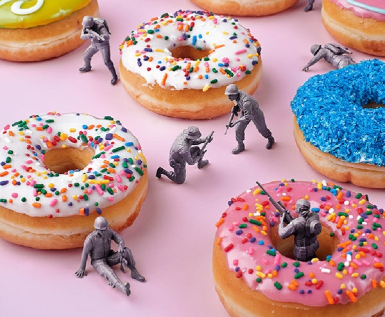 Image – Colorful and well-glazed donuts provide coverage for soldiers engage in a vicious food fight. Hiding around donuts and in donut holes, they shoot at each other
