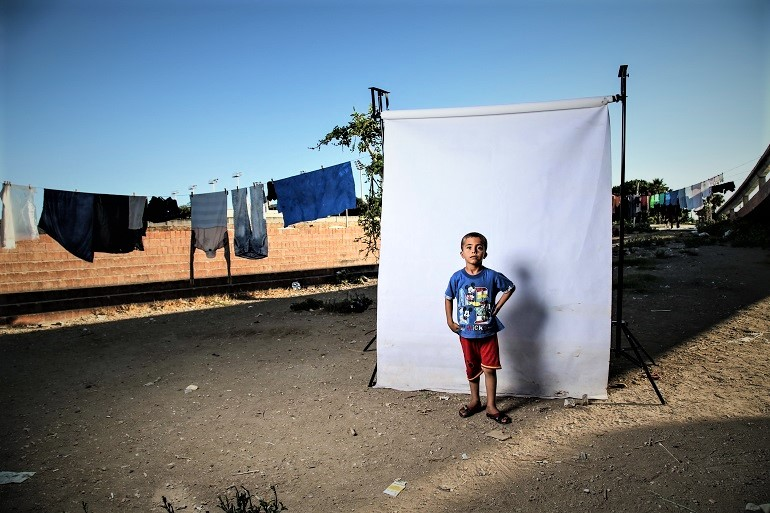 Image: Photograph of a Boy wearing a red polo tee shirt with Mickey Mouse prints in front of a white background is one of the photographs by Iranian photographer Amir Kabir Jabbari highlighting the lives of Syrian Civil War children