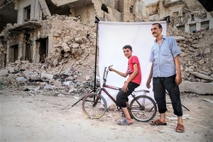 Image: Photograph of boy on a bicycle and a man in front of a white background is one of the photographs by Iranian photographer Amir Kabir Jabbari highlighting the lives of Syrian Civil War children