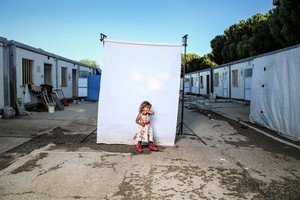 Image: Photograph of a girl wearing sleeveless dress with flower motifs and red shoes in front of a white background is one of the photographs by Iranian photographer Amir Kabir Jabbari highlighting the lives of Syrian Civil War children